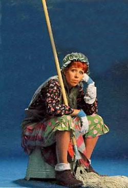 Carol Burnett dressed as the Charwoman with mop seated on overturned mop bucket