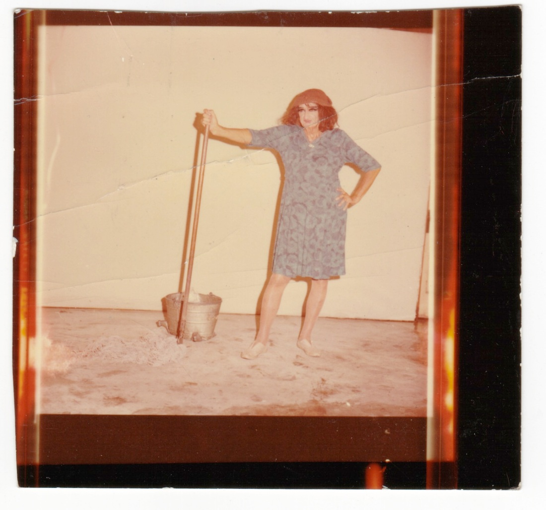 "Color photograph of Ray as the ""Mop Woman"" in a blue housedress with mop and bucket"